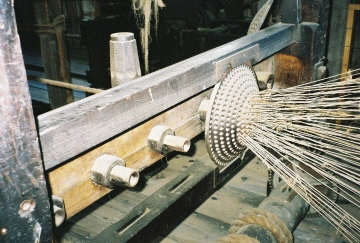 Individual yarn threaded into machine to form strand